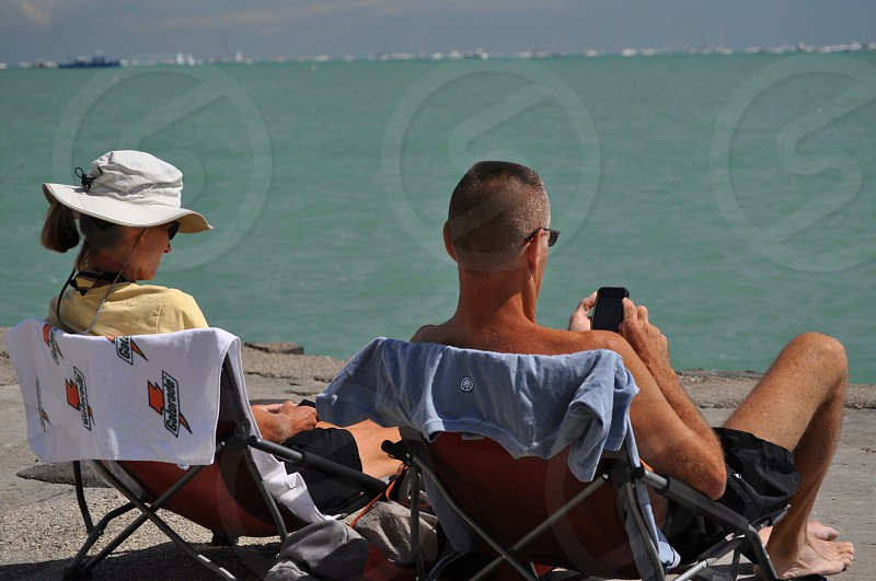 couple sitting on folding chair using their smartphones at the beach photo