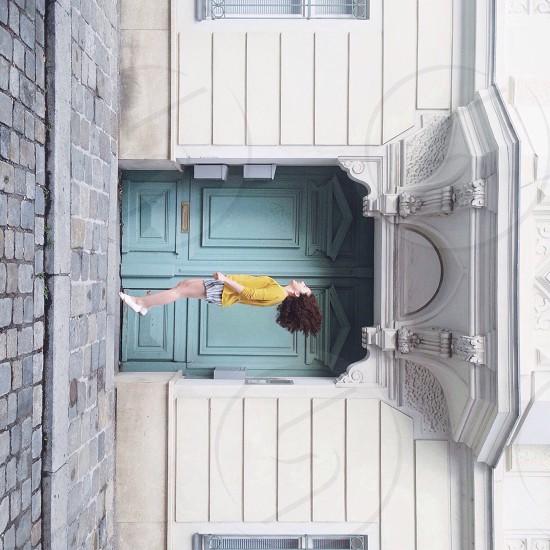 woman wearing yellow long sleeved dress jumping photo