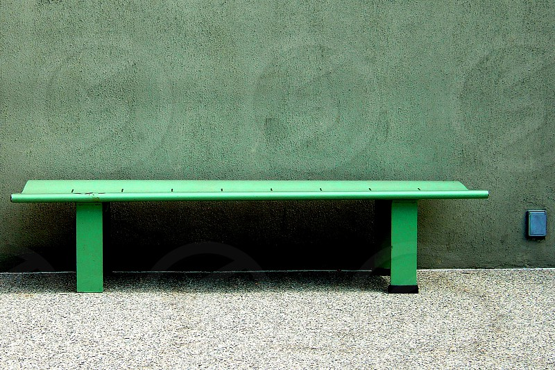 A simple green wooden bench stands outside on the sidewalk against a textured green wall. photo