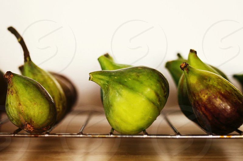 A line-up of harvested fig on the wooden kitchen counter. photo