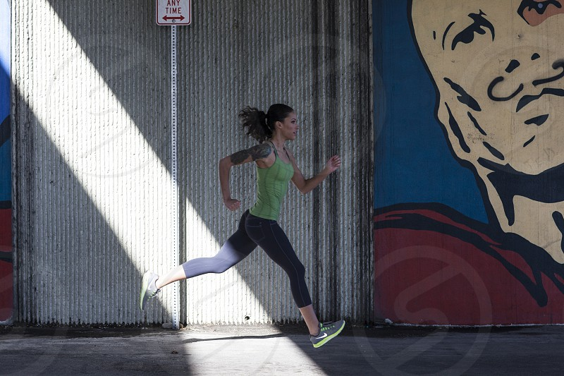 urban wall painted wall running fitnessgirl runningstrengthpowerstridecity streets photo