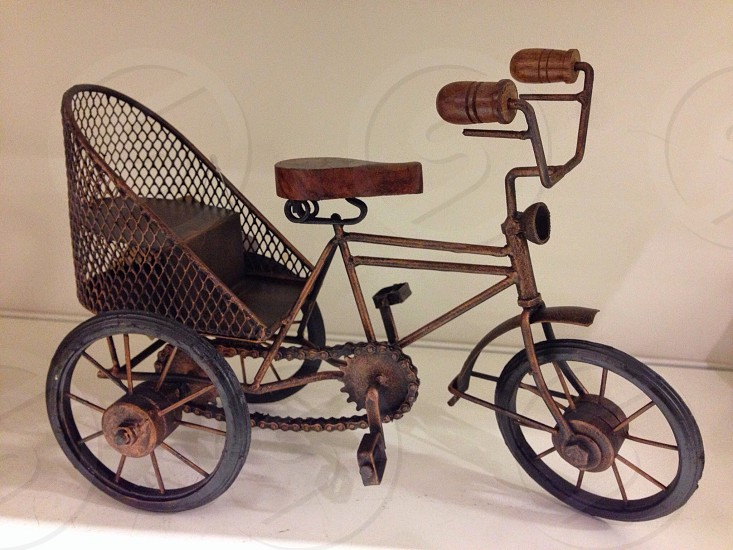 brown vintage tricycle with brown wooden bicycle seat photo