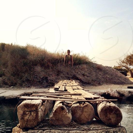man standing neat brown wooden footbridge photo