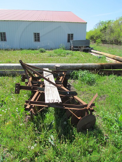 Old rusty vintage disc plow with barn in the background. Antique. Plowing farm farming grass shed machinery photo