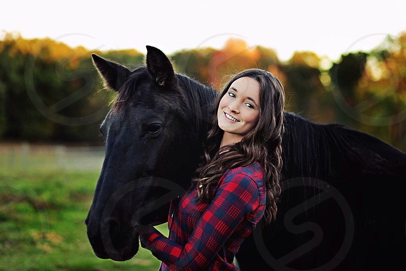 woman smiling standing with a black horse photo