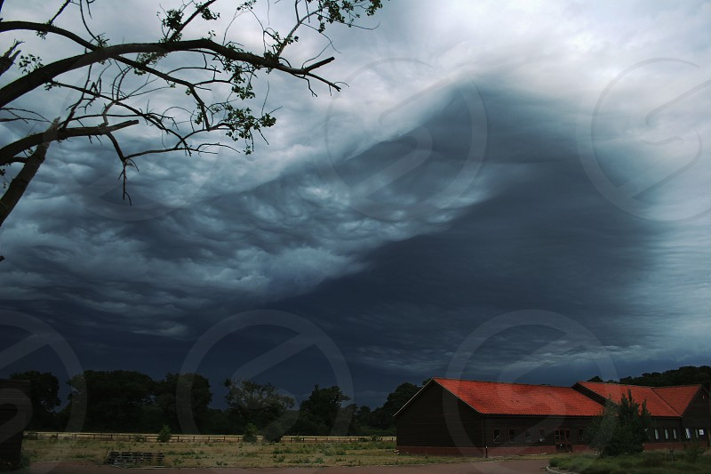 storm storm clouds grey clouds clouds mamatus clouds storm front farm barn trees dark clouds stormy bad weather photo