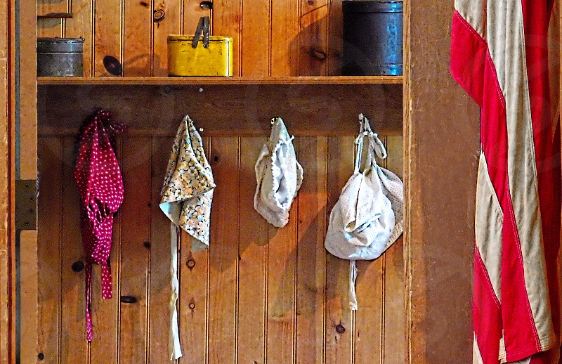 Vintage bonnets and lunch pails are seen in an old fashioned school cloak room next to an American Flag photo