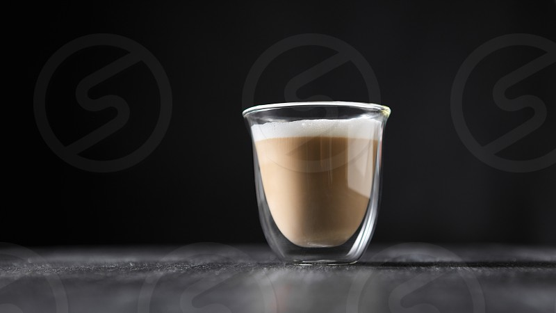 Freshly brewed cappuccino with foam in a glass cup on a black wooden table around a dark background with copy space. photo
