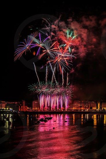 fireworks display with reflection on water photo