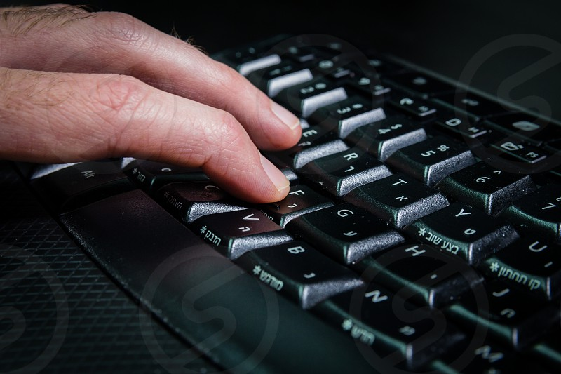 Man typing on a keyboard with letters in Hebrew and English - Wireless keyboard - Dark atmosphere photo