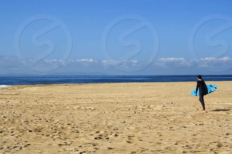 In the distance a surfer carries a surfboard and walks across a sandy beach to the ocean photo