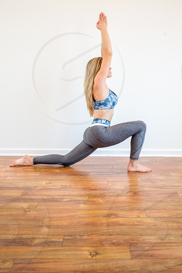 woman in blue and white sports bra bending knees and raising hands photo