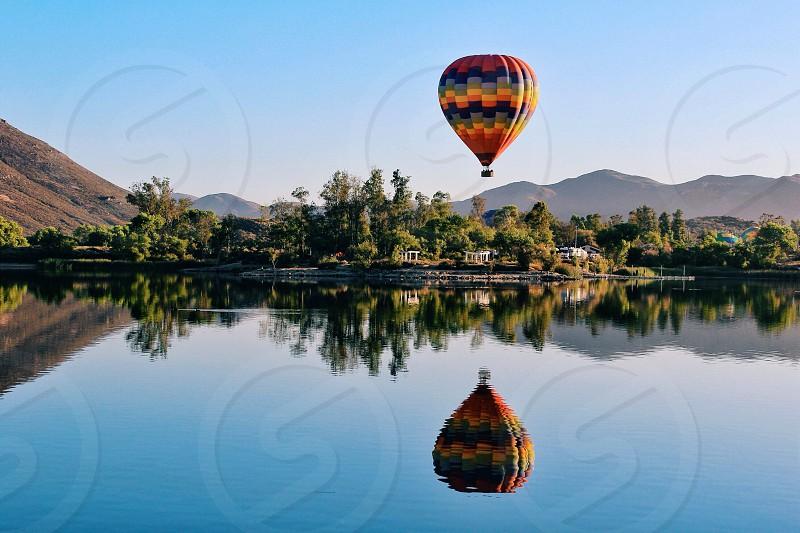 hot air balloon above lake and green trees photo