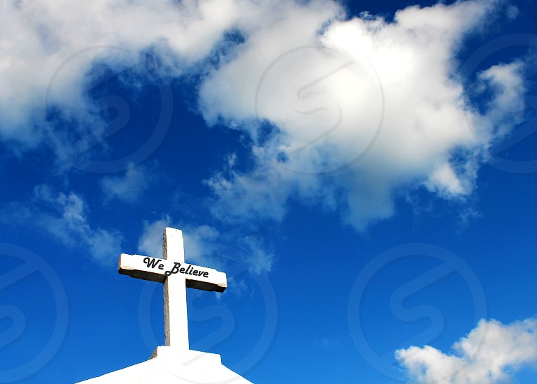 """White cross with the words """"We Believe"""" against a ble sky with white clouds. photo"""