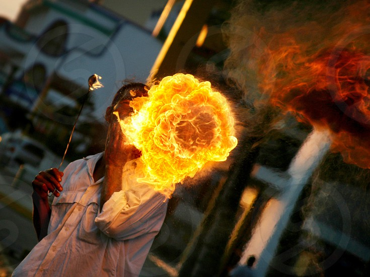 A street performer blows a giant yellow orange fireball toward unsuspecting tourists in Mexico. Flame Explosion Fuel Blast Heat Hot. photo