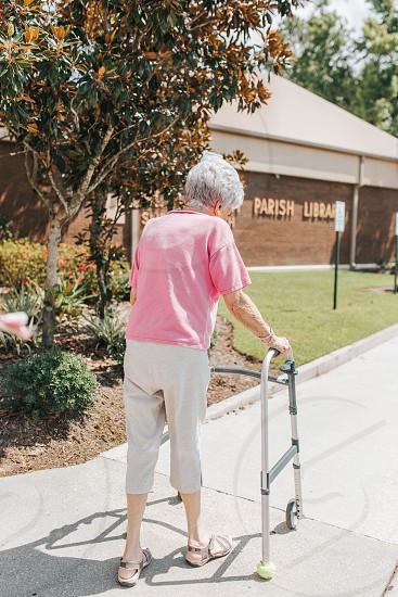 95 year old woman walking using a walker photo