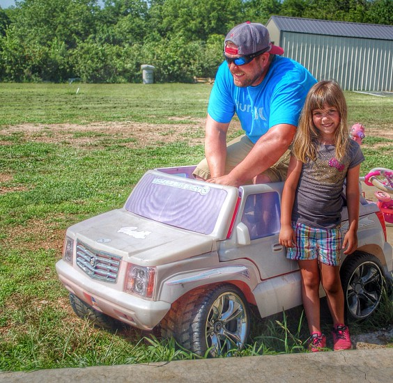 """My husband """"driving """" my daughters' Barbie Escalade. photo"""