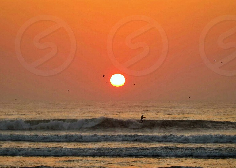 landscape photograph of surfer on beach waves on a golden hour setting photo