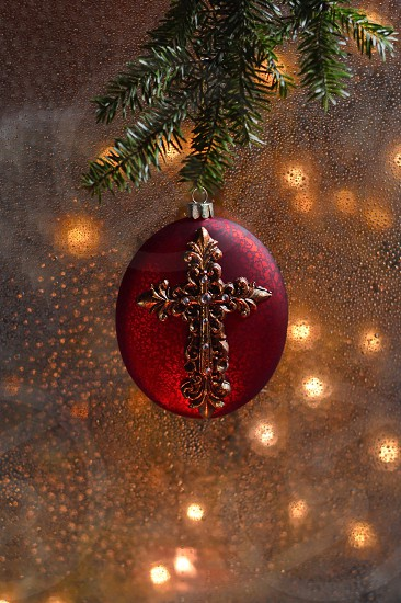 Red Christmas ornament with a cross against a window and Christmas lights photo
