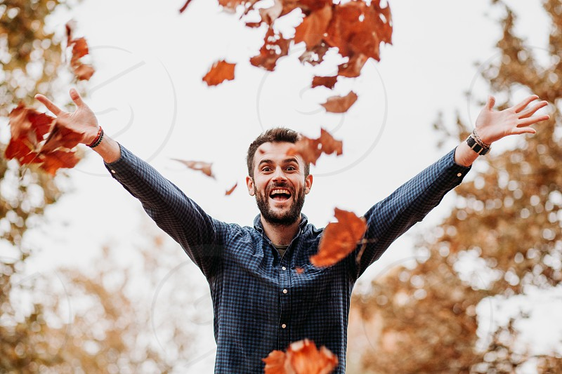 Young man throwing autumn leaves in the air photo