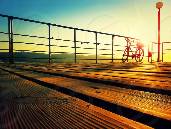 Silhouette of a bicycle on a seaside deck in the morning. Golden sunrise over the sea coast. Lifestyle background on the Sunny Beach Nessebar Bulgaria. photo