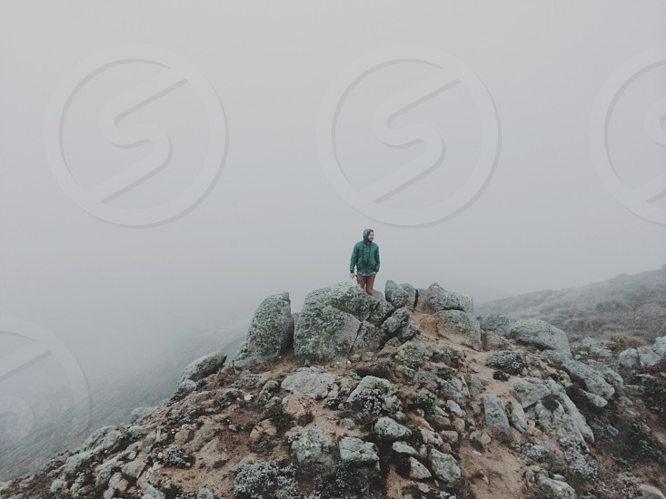 person in blue jacket on top of grey rocks photo