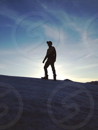 man walking on brown sand photo