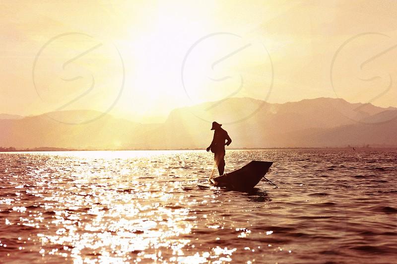 man standing on boat fishing photo