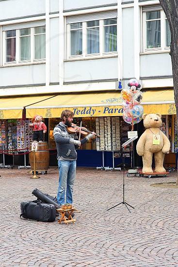 brunet bearded man wearing gray black knit  sweater playing violin on cobblestone town courtyard photo