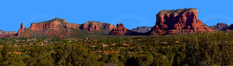 The Village of Oak Creek beneath the majestic red rocks of Sedona. The red rocks in the panorama consist of Castle Rock on the far left Bell Rock in the center and Court House Butte on the far right. photo