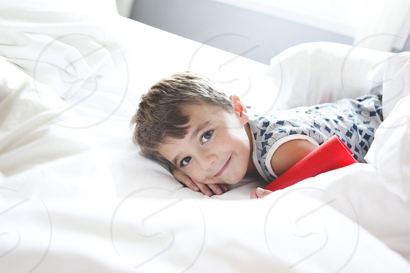 boy reclining on white bed wearing grey and black tank top portrait photo