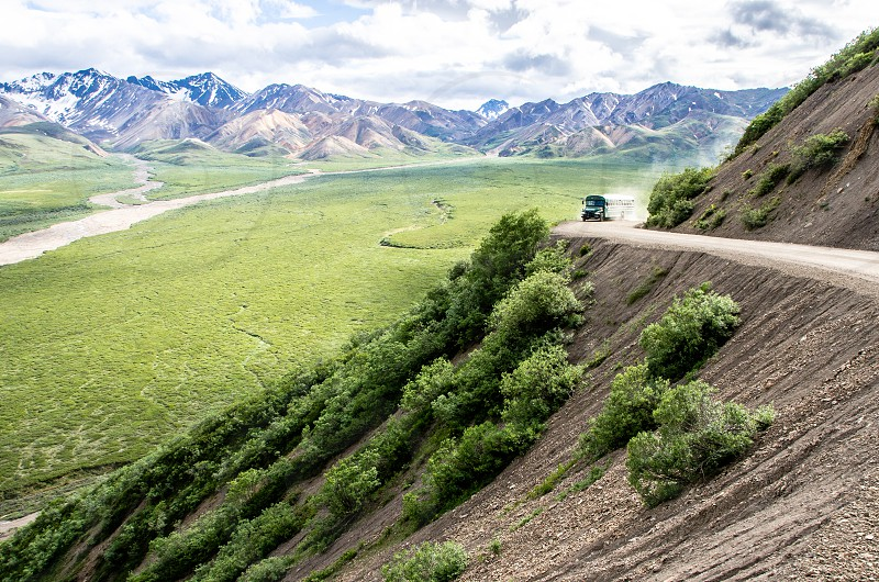 Summer time tourist discover the remote wilderness of Denali National Park Alaska. Bus travel along dirt road on side of valley. photo