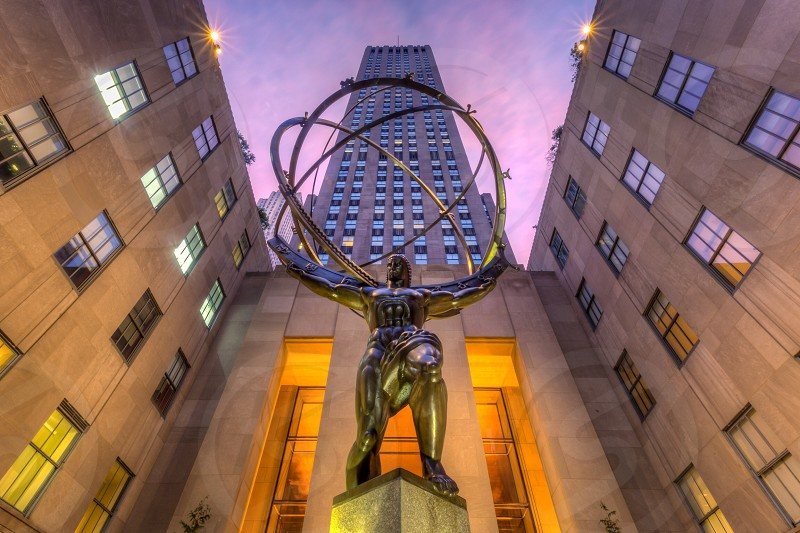 statue of man holding sphere in front of concrete building photo