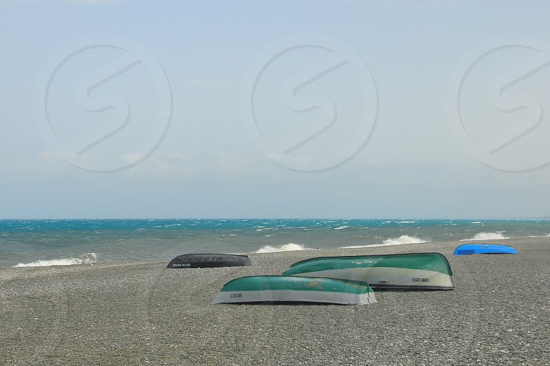 green blue and black boat tumbled down on shore line photo
