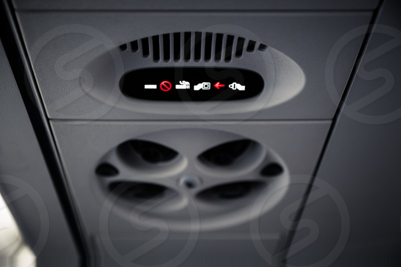No Smoking and Fasten Seatbelt sign Inside an airplane. Overhead console in the modern passenger aircraft photo