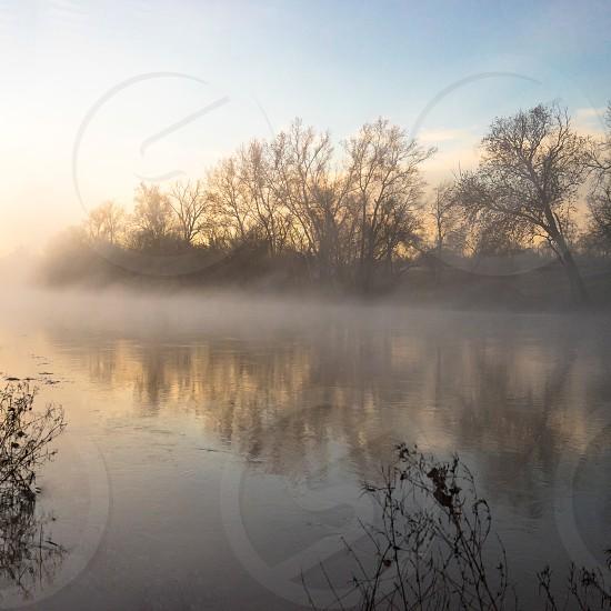 Morning sunrise and fog over peaceful river. photo