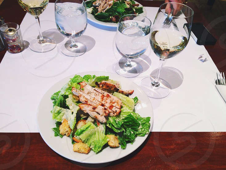 white ceramic plate with food near clear long stemmed wine glass photo