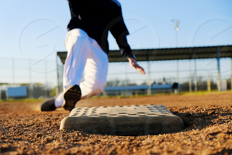 Baseball player slides into base on the field. photo
