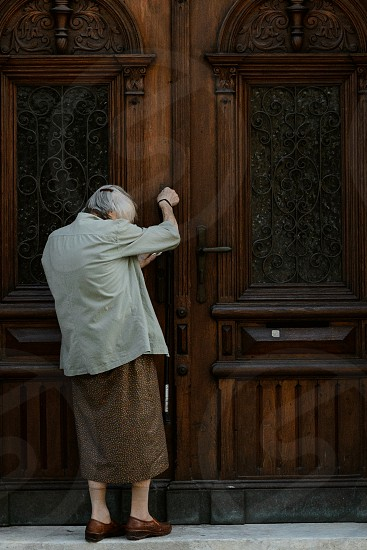 Beautiful old lady entering a majestic door in the streets of Ljubljana.  photo