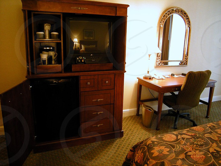 Hotel room beige walls entertainment center with coffeemaker refrigerator and desk photo