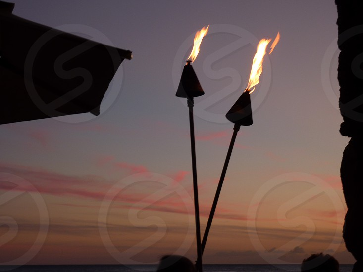 torches at sunset sunset fire hawaii photo