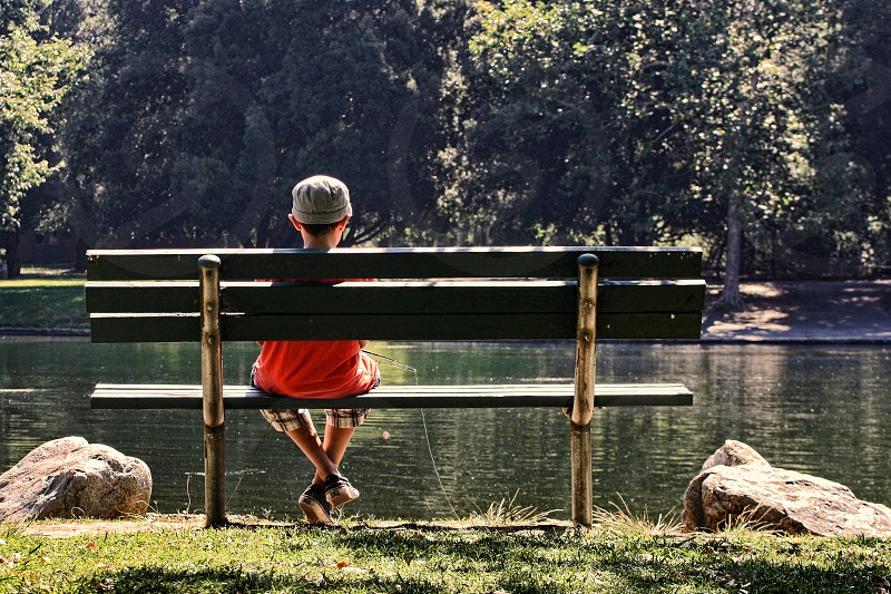 Seen from behind and back lit a boy sits alone on a park bench and fishes in a pond. photo