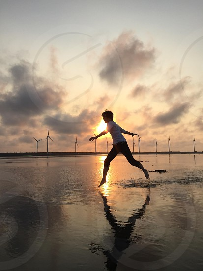 boy jumping on sand filled with water photo