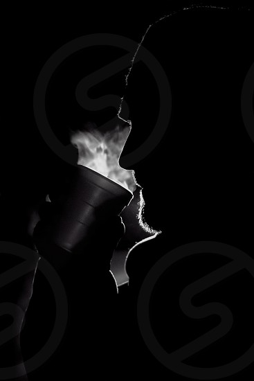 silhouette photography of man drinking on the cup photo