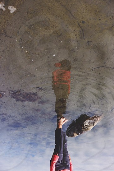 person in red long sleeve shirt standing in water photo