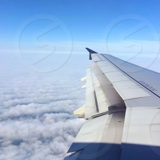 white and gray airplane hovering over white clouds photo
