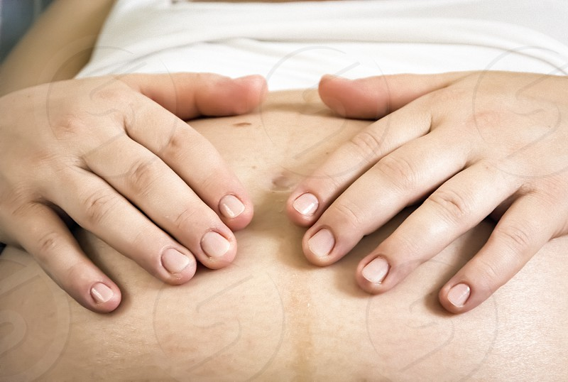 Hands of a pregnant woman caressing her belly. New life concept photo
