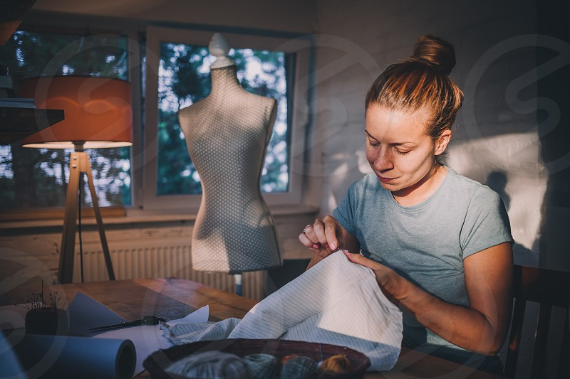 Professional dressmaker designer making a costume at atelier. Fashion and tailoring concept  photo