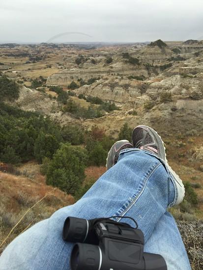 black binocular on person's blue jeans photo
