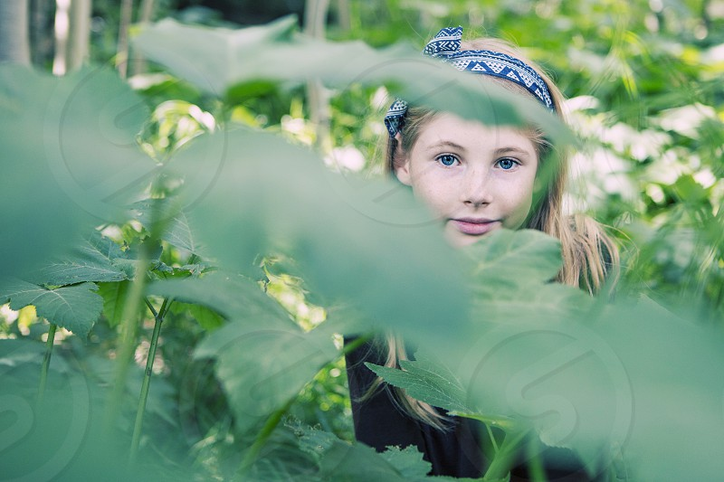 childkid girl 9 years old blonde long hair head band bow nature green aspens colorado mountains sweet innocent portrait natural lighting pretty little girl smile blue eyes brown shirt landscape trees wild hiking exploring playing outside hiding hide and seek play peekaboo confident shy photo